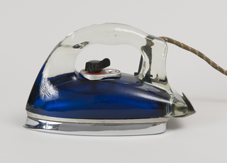 """Broad, oblong wedge-shaped profile comprising one-piece molded transparent glass shroud and handle affixed to white metal soleplate and heel rest. Interior of shroud painted with metalic looking blue emulsion. Fabric-covered power cord emerges from tubular rubber flange at top right side. Black plastic dial on red face-plate inscribed:  """"Off, On, Rayon, Silk, Wool, Cotton, Linen,"""" and """"Low, Med, High."""""""