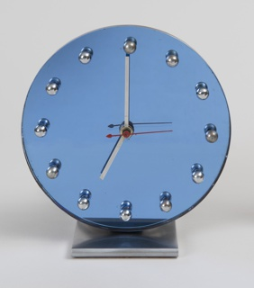 Circular blue mirror glass disc on rectangular, matte-finished chrome-plated base with curved edges; face with twelve chrome-plated spheres in place of numbers; long, narrow rectangular hour and minute hands; red, needle-like second hand.