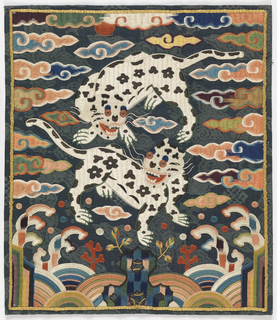 Rectangle of dark green damask heavily embroidered in bright polychrome silks in design of two spotted dogs amid stylized cloud forms. The dogs' eyes are of couched gold (wound on thread core); a border of couched gold (gilt paper on heavy thread) surrounds the picture, which resembles a Chinese rank badge. Backed with paper and lined with thin blue silk.