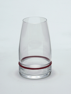 "Clear blown glass. Beaker/water glass.  Flat based beaker of cylindrical shape; sides curve inward toward lip. Side waisted above base to hold silicone ""bumper"" ring: set of silicone rings in plum, black, and white supplied with set."