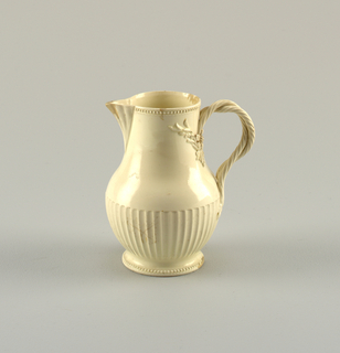 Pear-shaped, footed, with ribbed and pointed spout. Lower half ribbed. Pearl band at lip and foot. Forked handle terminates in raised leaves and flowers.