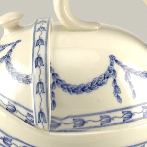 A white porcelain teapot and lid that appears to be an egg shape.  The teapot's handle is on the top half and on the other side is the teapot's lid. Below the handle are two small white feet off the side. The lid is a wedge shape about 1/6th of the circular form that can be removed. Inside the pot, there is a top chamber with a straining system and the bottom chamber. The outside of the teapot is decorated with a blue patter of flowers and hanging leaves.