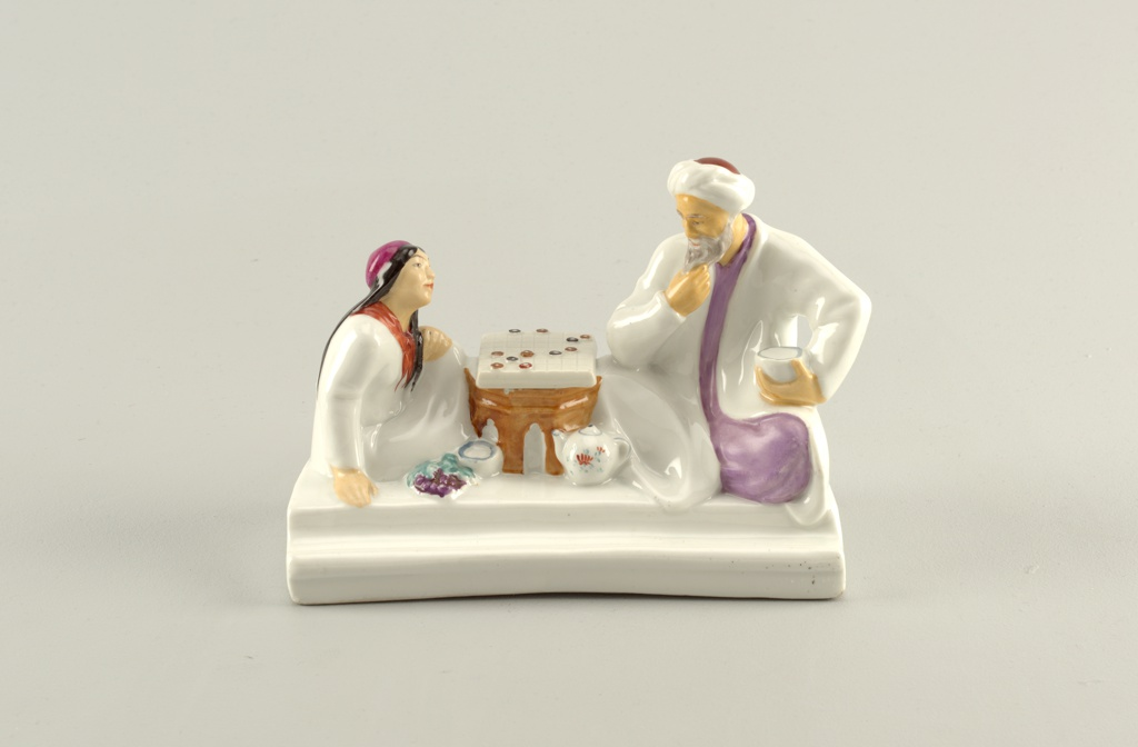 Two figures playing chess: young girl seated on left, left hand on raised knee, wearing red cap and neckerchief; older man with turban, robe seated at right side of chess board, right hand at chin/beard, holds a small bowl in left hand; teapot, bowl, and grapes rest on floor, rectangular base with indentation for pens along front edge; inkwell underneath chess board.