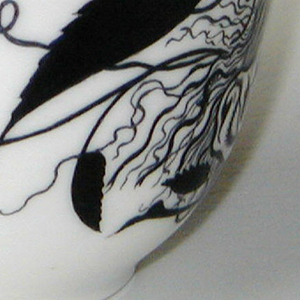 Cylindrical, with rounded bottom, slightly flaring to lip, loop handle withmolded foliate pattern at joining to body; painted with black and gilded rose blossom, leaves, grotesque mask around sides; thin gilded and black band around rim