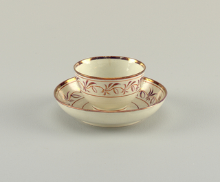 Circular cup and saucer bordered with an undulating vine in red showing leaves and fruit. Detailed in copper lustre.