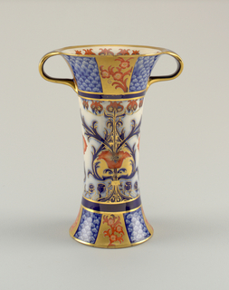 Tall vase with flared flat base and flared upper lip. Lip continues with two curved applied handles. Underglaze blue decoration of scroll patterns at base and upper section, stylized foliage at center. Enamelled red flowers overglaze, with gilded edges and ground panels.