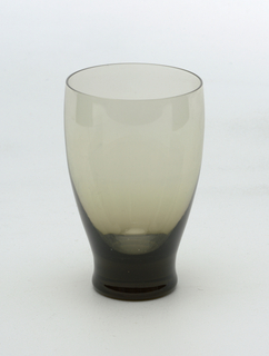 Smokey gray glass with curved sides and solid tapered foot.