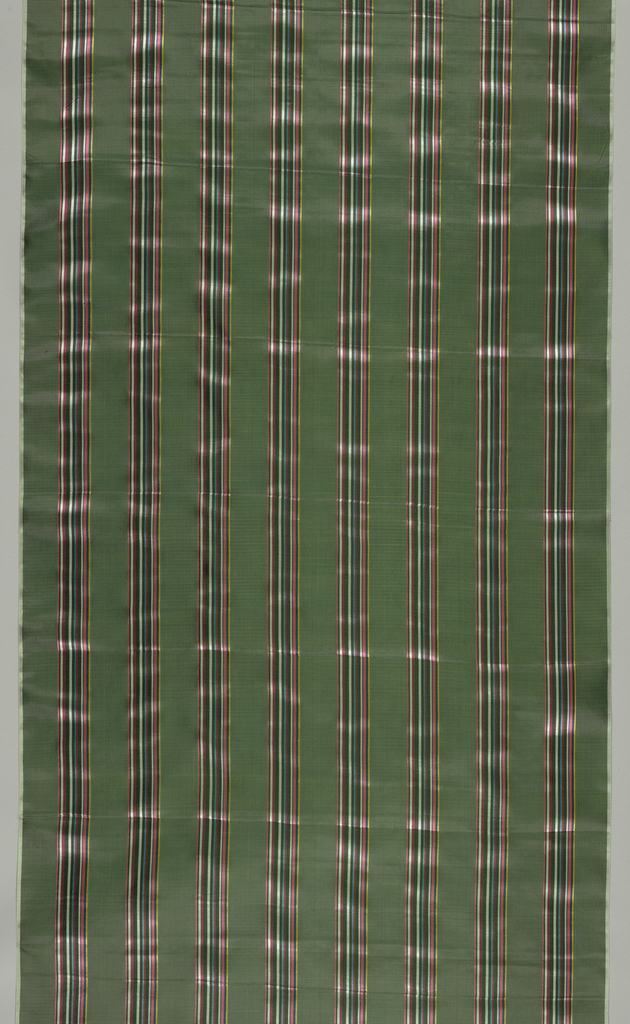 Dark green cloth ground with groups of pencil stripes in yellow, blue, black, pink, purple, white warp twill at five centimeter intervals. Two white plain cloth selvages.