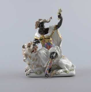 """Africa"" female figure, black, with elephant-head coif, feather tunic and legings, holding sheaf of wheat; seated on crouching lion, facing left."