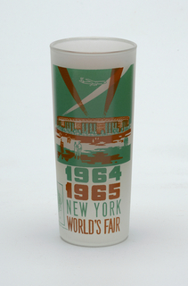 "Tall, slightly tapering cylindrical form of clear ""frosted"" glass with aqua and brown enamel decoration showing the William A. Shea Stadium, ""1964/1965/NEW YORK/WORLD'S FAIR,"" and Unisphere logo; brown panel with brief paragraph about the stadium on reverse."