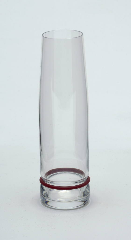 "Clear blown glass. Beaker/champagne flute.  Flat based tall cylindrical shape; sides curve in-ward toward lip. Side waisted above base to hold silicone ""bumper"" ring: set of silicone rings in plum, black, and white supplied with set."