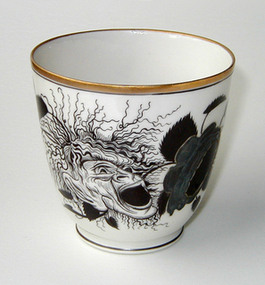 Body cylindrical with slightly rounded bottom and flaring towards top; loop handle; painted with rose, leaves, and grotesque mask face in black, gilding and silvering; thin gilded and black band at top edge and black band at base