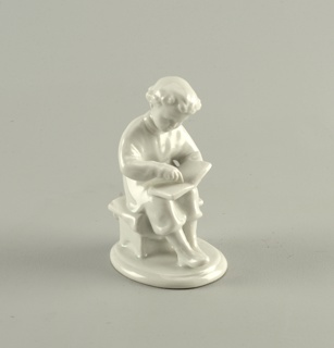 A young boy sits on a stool reading with book in lap; small round base; unpainted