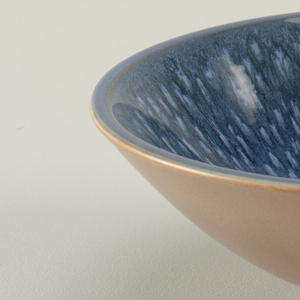 Circular bowl tapering to short circular foot; blue speckled interior.
