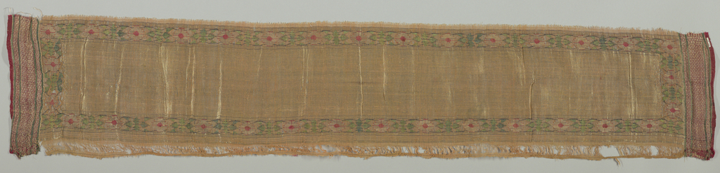 Rectangular panel with a border design of conventionalized blossoms and leaves in green, red and blue with silver threads. Two ends are striped red, green and red and gold.