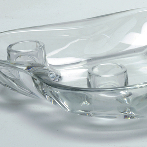 Clear glass, irregular four-lobed oblong shape, upcurved with short sides. Four candleholders, one at each lobed section.