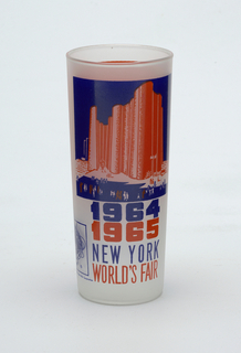 "Tall, slightly tapering cylindrical form of clear ""frosted"" glass with dark blue and orange enamel decoration showing the Hall of Science, ""1964/1965/NEW YORK/WORLD'S FAIR,"" and Unisphere logo; orange panel with brief paragraph about the Hall on reverse."