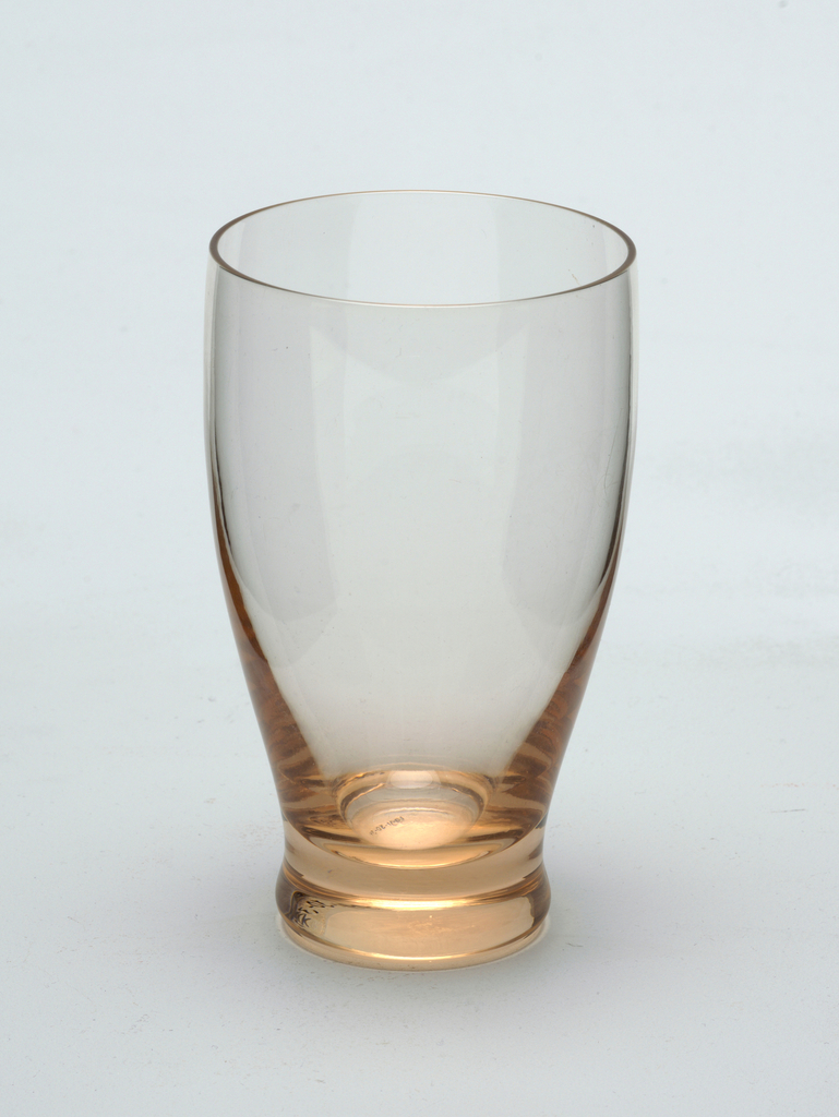 Peach glass with curved sides and solid tapered foot.