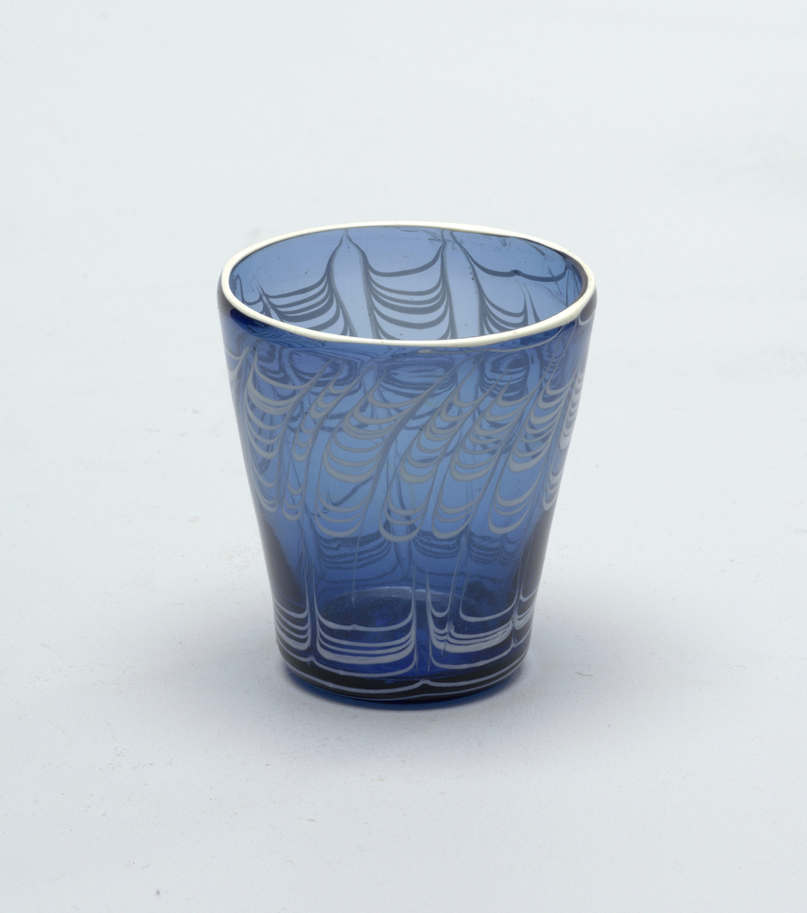 Blue glass beaker with opaque white glass decoration in a horizontal flame pattern.