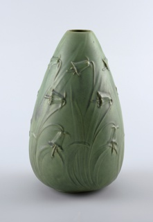 Moss green vase with relief daffodils. Buff colored clay body, cast. Large ovoid body on low flat foot; no neck. Body modeled in relief with three tiers of large pendulous bell flowers and leaves (daffodils?). Allover light and dark green matte glaze, with the clay body revealed at the high points in the relief. Bottom and interior glazed.
