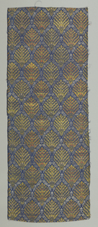 Medium-sized repeat of stylized symmetrical flower sprays of gold with touches of pale pink and coral in a trellis framework of fine silvery leaves and flowers on dark blue ground. Silver and gold threads are now much worn revealing white and yellow silk cores respectively. Cord selvage of bunched salmon-pink silk.
