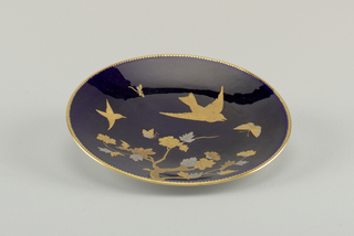 Round plate with blue glaze ground. Pressed gold paste decoration of birds and flowering branches. Scalloped gilt border.