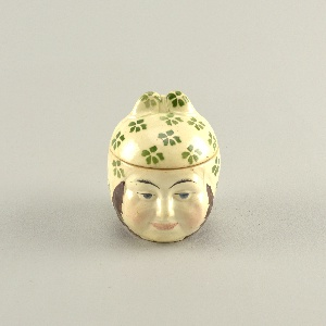 In the shape of the head of a woman wearing a kerchief ornamented with green stylized flowers