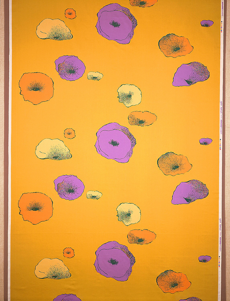 Abstract floral forms, each with a shaded depression in the center, in purple, orange and pale yellow scattered over a bright chartreuse ground.