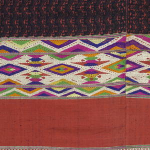Red cotton panel, probably a sarong, brocaded in all-over black zigzag pattern. One end elaborately decorated with wide band, running full width, embroidered in white, pink, green, yellow, blue, and gold. Another band of plain red follows. Two widths pieced in the middle.