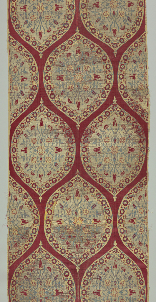 Woven textile with overall large-scale ogival medallions on a red ground. Each ogee containing a symmetrical arrangement of tulips and carnations in red, yellow, and light blue on a silver ground, surrounded by a floral vine border.