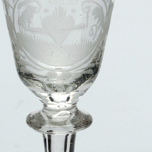 Clear glass goblet.  Vessel is inverted bell shape with etched decoration.