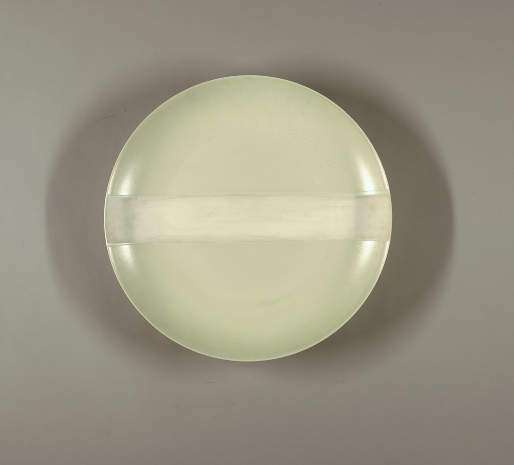 Large circular thrown plate. Concave center, with upturned edge, plain rim. Double foot ring underside. Glaze with pale greenish-white semi-matte glaze. Across center of obverse, a 9 cm. wide unglazed strip.