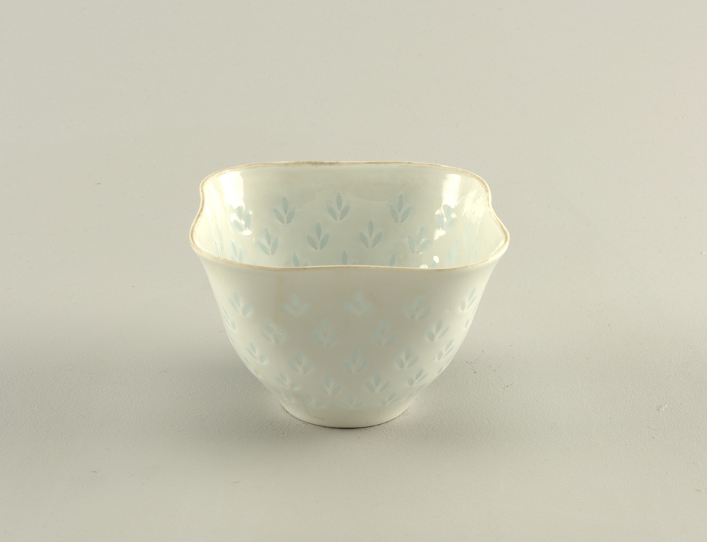 """Bowl is of squared form with curved corners. Circular foot right supports flared oval undulating bowl, which tapers outward toward plain lip. Overall pattern on body walls of three-leaf motif, pierced through body and filled with translucent glaze in """"riceware"""" technique."""