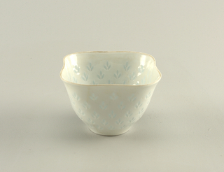 "Bowl is of squared form with curved corners. Circular foot right supports flared oval undulating bowl, which tapers outward toward plain lip. Overall pattern on body walls of three-leaf motif, pierced through body and filled with translucent glaze in ""riceware"" technique."
