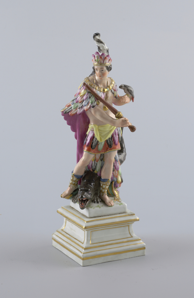 """"""" America"""" standing male figure, wearing feather belt, long cape and headdress, holding sceptre and parrot; attributes: crocodile and cornucopia. Square pedestal. Underglaze mark: sceptre. Forming a set with 1960-1-44a,b,c"""