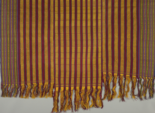 "Panel or blanket used as dress for women; dark red handwoven cotton, with horizontal rib, decorated with stripes brocaded in yellow, in the warp. Piece consists of three breadths, 17 1/2"" wide in the center, 19 1/2"" wide at the sides. Side panels woven with group of shaded stripes and narrow brocaded patterns. Warp fringe of yellow and red."