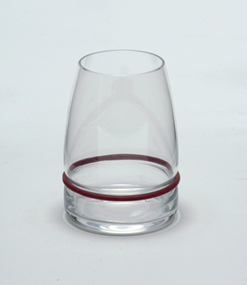 "Clear blown glass. Beaker/wine glass. Flat based beaker of cylindrical shape; sides curve inward toward lip. Side waisted above base to hold silicone ""bumper"" ring: set of silicone rings in plum, black, and white supplied with set."