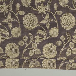 Dark purple satin ground with closely-spaced serpentines of slender branches with large conventionalized flowers, fruit, and foliage brocaded in gold metallic thread.