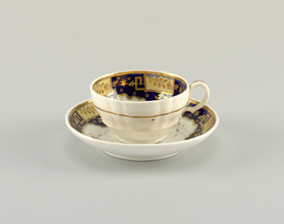 Double-bellied cup with vertical ribbing and simple Bristol handle. Cup and saucer have underglaze blue band with cream-colored panels bordered and ornamented in gold. Gold circle and floral pattern on white reserve.