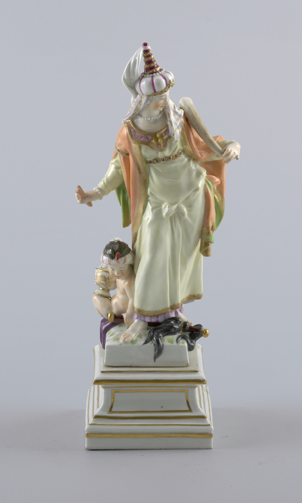 """""""Asia"""" standing female figure, wearing turban and holding pieces of cinnamon and an elephant tusk; attended by seated, turbaned putto, holding censer and horse-tail sceptre; square pedestal."""