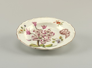 A plate with a wavy, brown-edged rim, painted with a large spray of pink and white crinum (Crinum Zeylanicum), with scattered sprigs and insects.