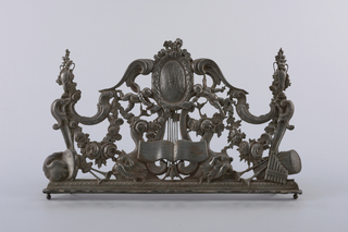 "Thin sheet of steel, cut out, repousse, engraved. Initials MA (Marie Antoinette)  in oval cartouche with wreath frame, surmounted by ribbon bow knot and supported by lyre with open music book. On each side: c-scroll designs, winged putti holding scrolls with names ""Lulli"" and ""Collase,"" dolphins, urns, musical instruments and festoons of roses. Two small ball feet, two folding supports in back; hinged music holder in front."