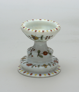 Footed Cup in opaque white glass.  Painted decoration of yellow and red flowers