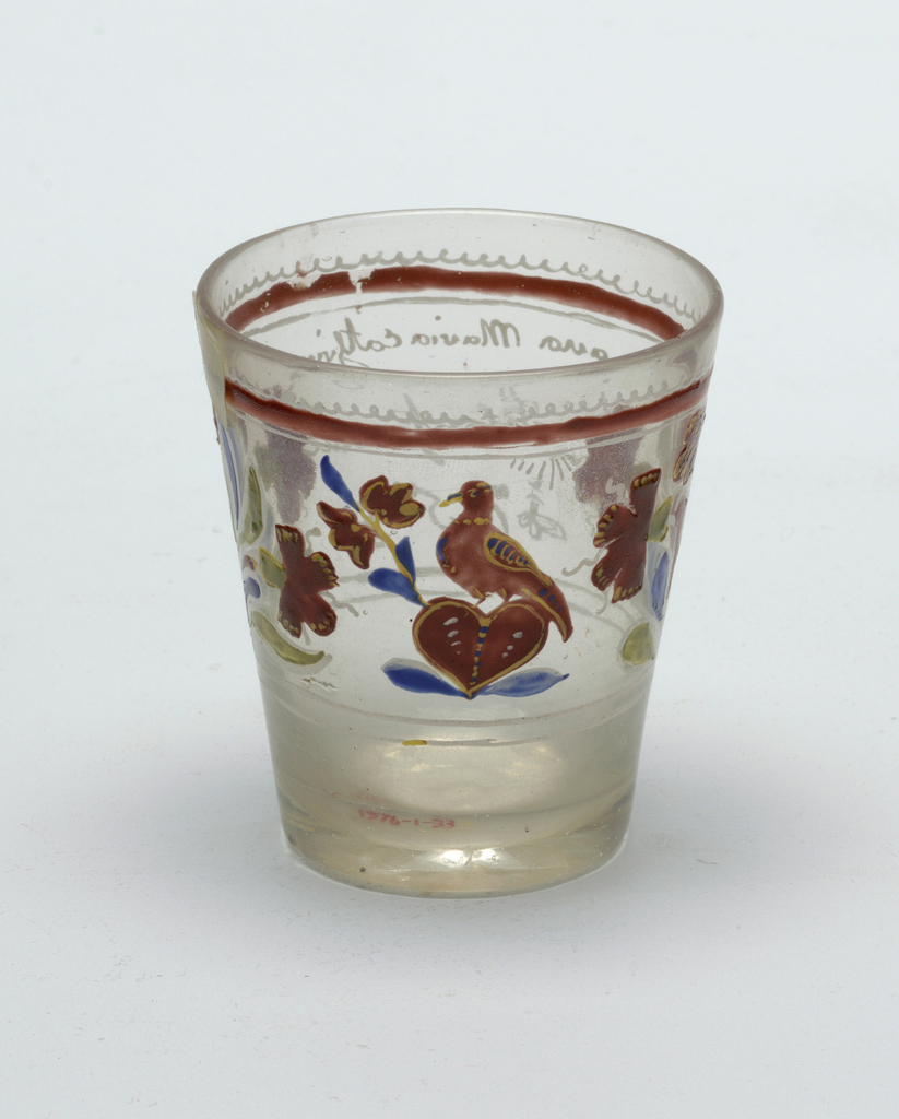 Clear glass beaker with slight gray cast.  Painted decoration Red bird perched atop heart central figure.