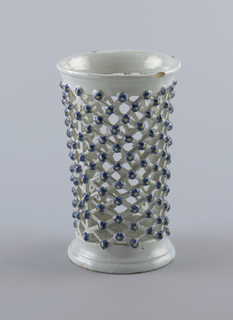 High pierced vase in the form of a lattice cylinder with flowers at the crossings.
