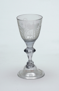 Clear glass goblet with light blue cast.  Creast etched on center of goblet