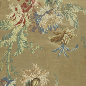 Two pieces of cream-colored satin brocaded with a design of broken stems and branches with flowers in blue, green, red, brown and black silks. Piece a is backed with white buckram and bound with gold and black striped velvet.