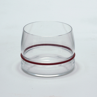 "Clear blown glass. Beaker/whiskey glass. Flat based beaker of cylindrical shape; sides curve inward toward lip. Side waisted above base to hold silicone ""bumper"" ring: set of silicone rings in plum, black, and white supplied with set."