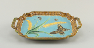 Rectangular tray with lobed upturned edges molded in basket weave pattern, glazed brown and green. Two handles similarly glazed. Center with blue ground and relief decoration of wheat in green and yellow, butterfly and flying insects in polychrome. Underside glazed in highly mottled sponged green, brown and yellow.