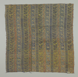 Striped textile with details in silver. Four repeated motifs within the stripes include Indian palm motif flowers and arabesques. Dark blue, green, pink and tan.